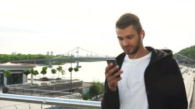 A cheerful guy is typing something in his phone