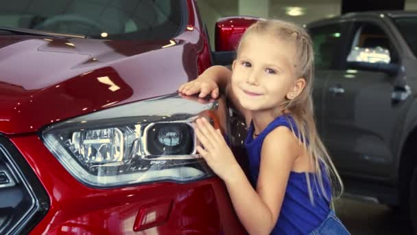 Beautiful little is girl posing on car background