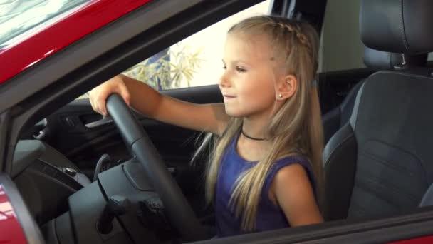 Krásná roztomilá dívka otáčí volantem automobilu