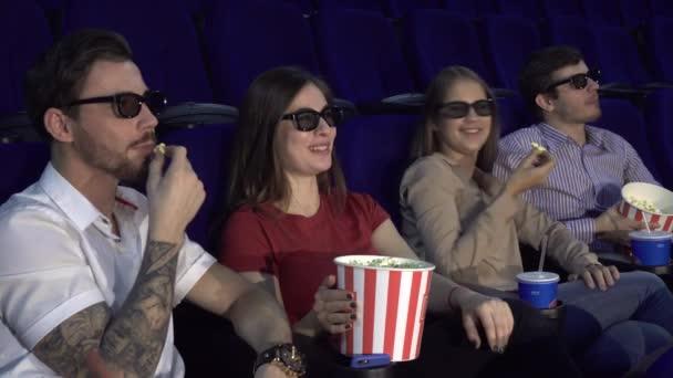 Zwei Paare im Kino sitzen und Essen popcorn