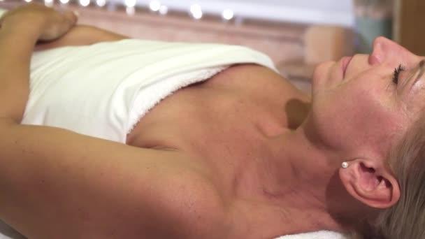 Uvolněná žena je na léčbu v lázeňském salonu