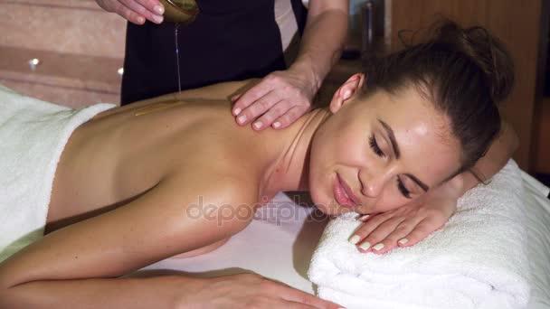 Profesionální masérka nasype krásné zákazníka s olejem a masáž ji