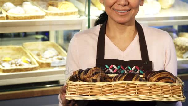 Cropped shot of a cheerful female baker posing with a basket full of croissants