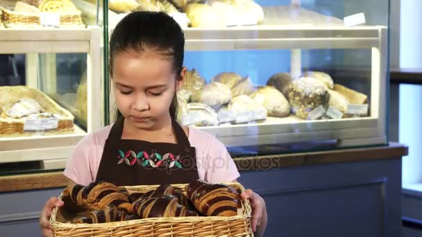 Cute little girl in an apron working at the bakery holding a basket with pastry
