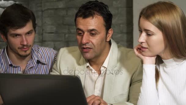 Reifer Geschäftsmann und seine jüngeren Kollegen arbeiten gemeinsam am Laptop