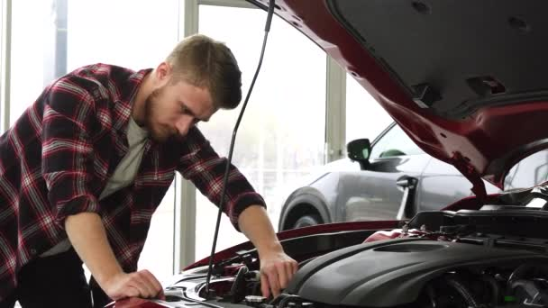 Handsome male cutomer examining engine of a car at the dealership showroom