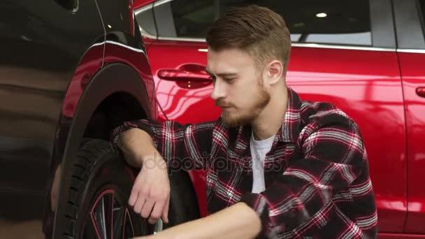 Mladý muž zkoumání kola a pneumatiky nové auto u dealera