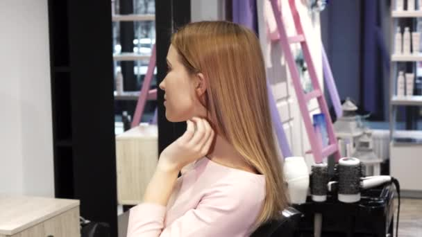 Gorgeous happy young woman with perfect long shiny hair smiling at the hairdresser salon
