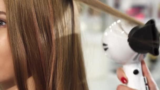 Oříznuté zblízka nádherná mladá žena dostává její vlasy stylizované v salonu