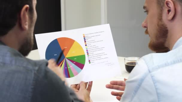 Close up of male business partners examining printed diagram