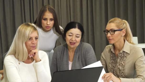 schöne junge Geschäftsfrau mit Laptop während eines Geschäftstreffens mit Kollegen