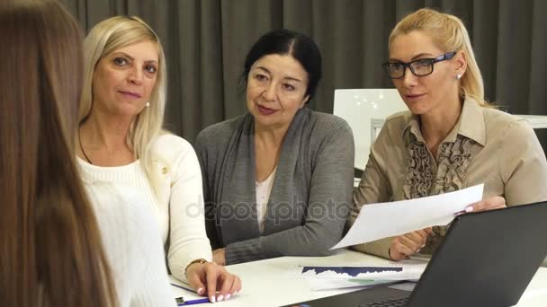 Three businesswomen interviewing new employee for job at the office