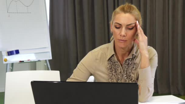 Attractive mature business woman working on her laptop at the office