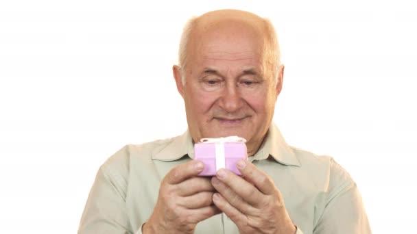 Šťastného starce usmívající se radostně napřáhl krabičky do fotoaparátu