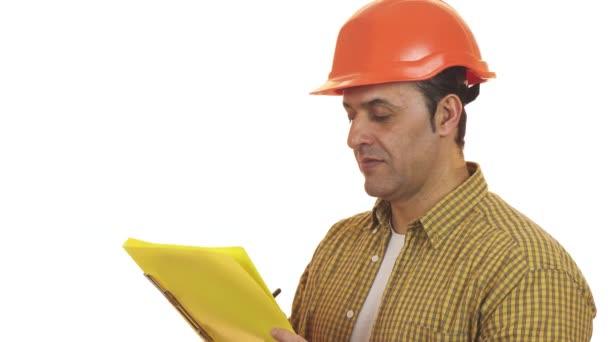 Reifer Vorarbeiter im Hardhat, der Notizen auf Klemmbrett macht