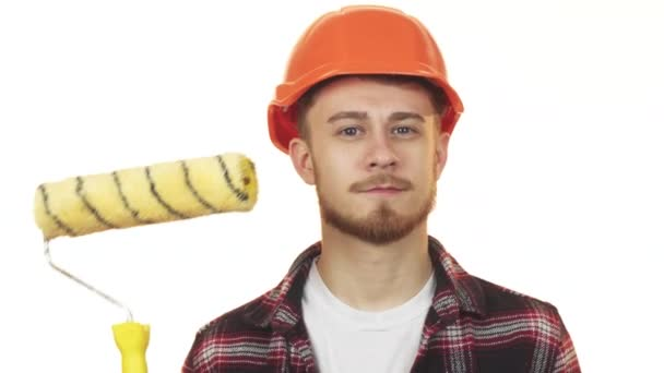 Happy young male builder holding paint roller showing thumbs up