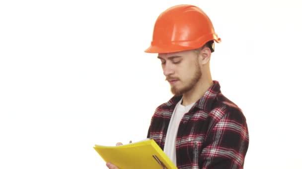 Mladí profesionální mužský dodavatele v bezpečnostní přilba poznámky s úsměvem