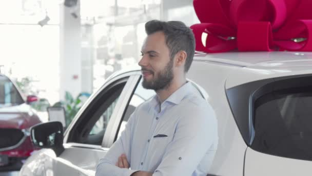 Attractive young man holding car keys to his new automobile at dealership