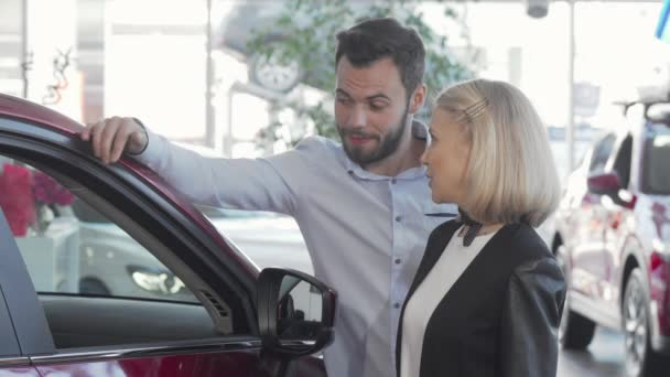 Happy couple choosing new automobile at the dealership