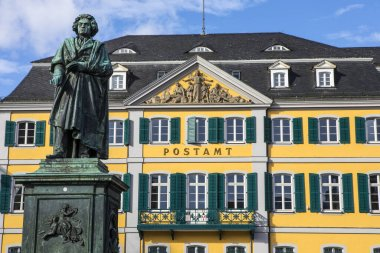 A statue of famous composer Ludwig van Beethoven - with the beautiful Old Post Office building in the background, located on Munsterplatz in the city of Bonn in Germany.