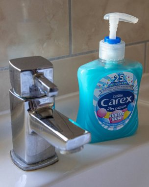 London, UK - March 12th 2020: Close-up of Carex Liquid Soap Hand Wash next to a tap in a bathroom.