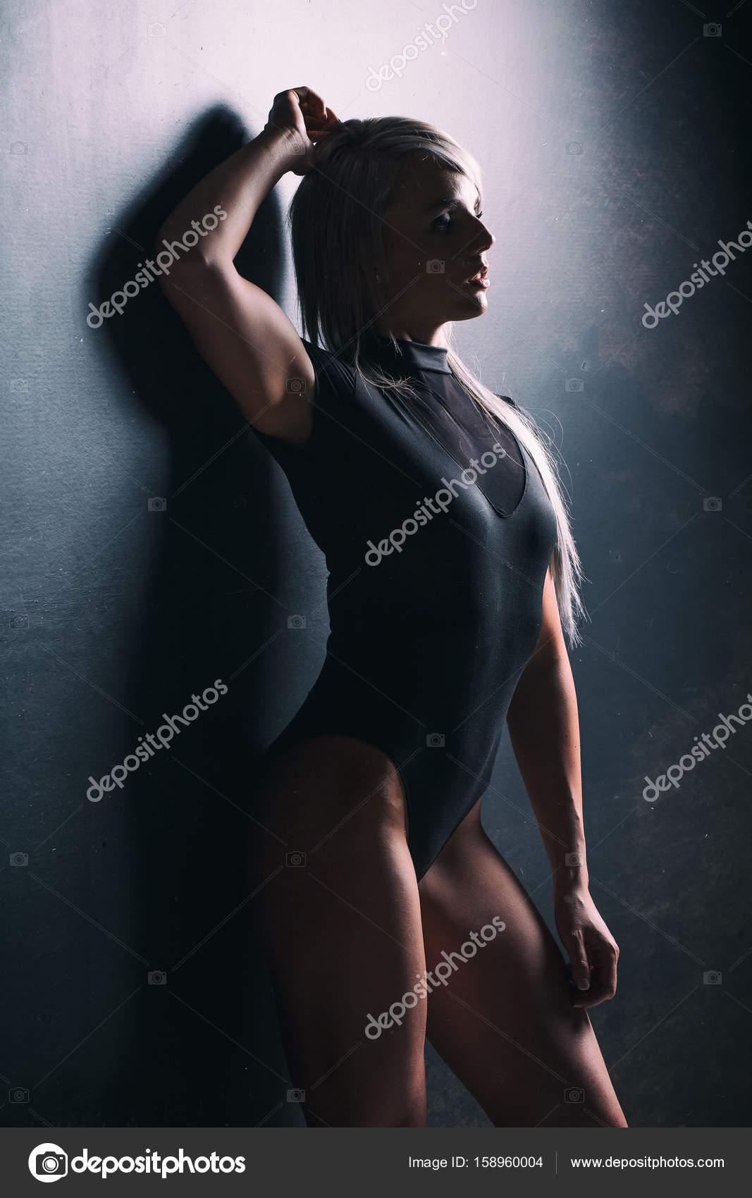 dramatic studio lighting. Sexy Female Fitness Model In A Studio With Dramatic Lighting And \u2014 Stock Photo