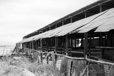 Wide angle view of old buildings and farm instruments on an old