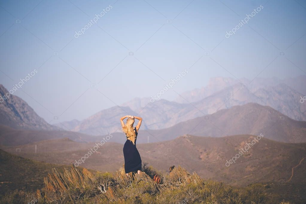 Rear view of beautiful blond female model standing in mountains enjoying the view