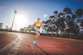 Fotografia Atleta di femmina fitness modello e pista Sprint su una pista di atletica in tartan