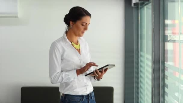 Young brunette female businesswoman working on smart device in boardroom