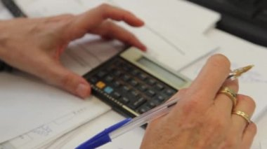 Close up of hands on calculator