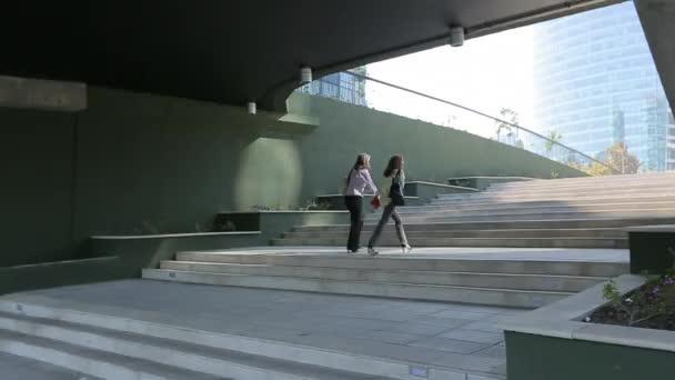 Ženy chodí nahoru po schodech před budovou