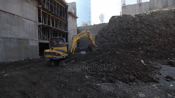 Excavator shovels dark soil and rubble on a construction site