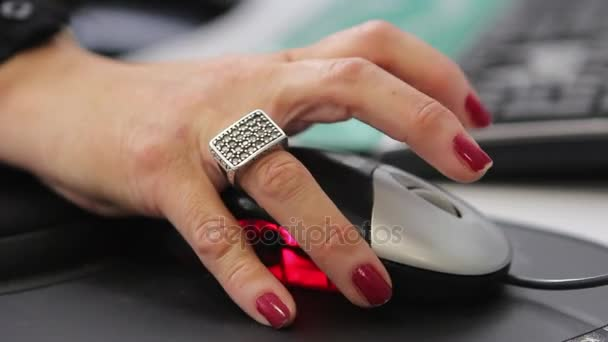A womans hand as she moves a computer mouse