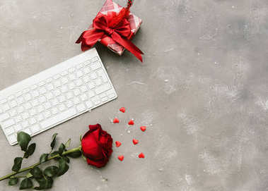 Flat lay composition with rose, keyboard and gift box
