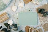 Fotografie Pracovní prostor. Svatební pozvánky, obálky řemesla, růžové a červené růže a zelené listy na bílém pozadí. Pohled. Plochá ležel, horní pohled svatební pozvánky šablony