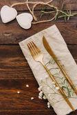 Fényképek Arany evőeszközöket vászon szalvéta. Rusztikus fa háttér táblázatban. Esküvő, vagy az ünnep fogalma