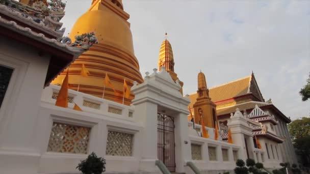 Fényképezőgép serpenyők a tetején egy gyönyörű arany sztúpa buddhista templom Bangkok, Thaiföld.