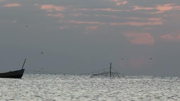 Rybářská loď plovoucí před východem slunce