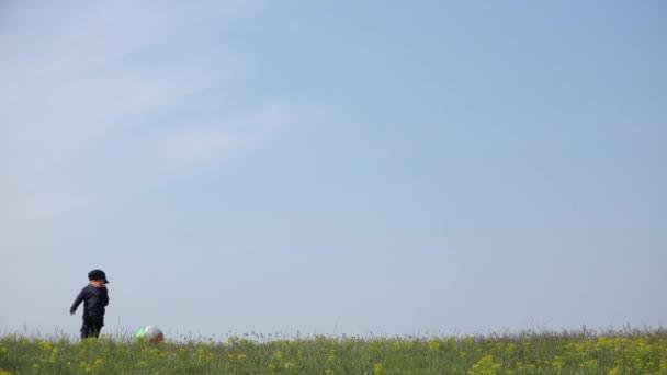 Malý chlapeček hraje s velkým míč na hřebenu kopce, klidnou oblohu nad 4k