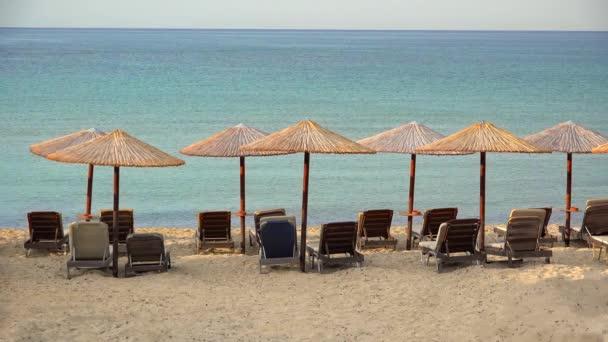 Prázdné exotická pláž s slaměné slunečníky a modré vody