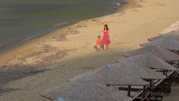 Beautiful mother holding little son hand walking barefoot on beach sand, evening