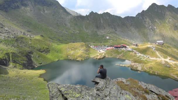 Mladý muž sedí na skále vyfotí jezero obklopené horami