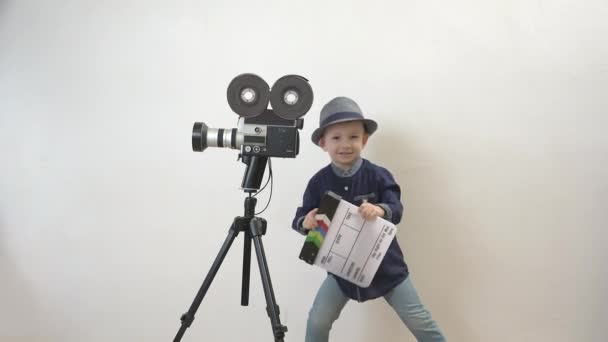 Funny child holding a clapboard, little director having fun, old camera, action