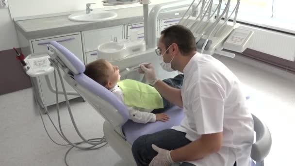 Mladý doktor konzultační malé dítě, portrét přátelské zubař a roztomilý kluk