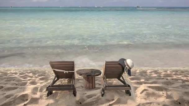 Two wooden sunbeds and table, hat hanging, exotic tropical beach for perfect summer holiday