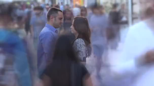 Young lovers couple stand still together in middle of fast moving crowded street, timelapse