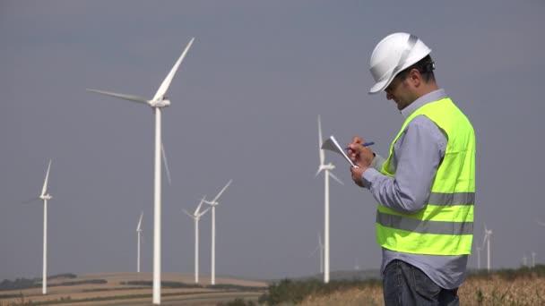 Inženýr v blízkosti větrných turbín psaní technické parametry