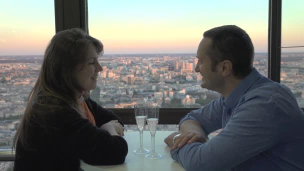 Romantische Feier auf der Hotelterrasse, Verliebte sprechen und lächeln, Prost mit Champagner, Blick auf die Stadt, schönes Abendlicht