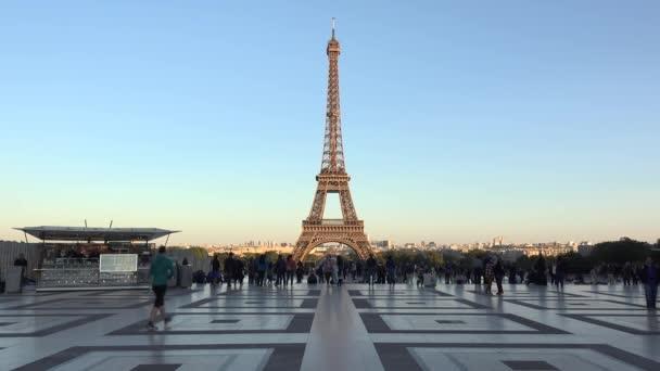 Eiffel tower on beautiful evening light, people passing on Trocadero